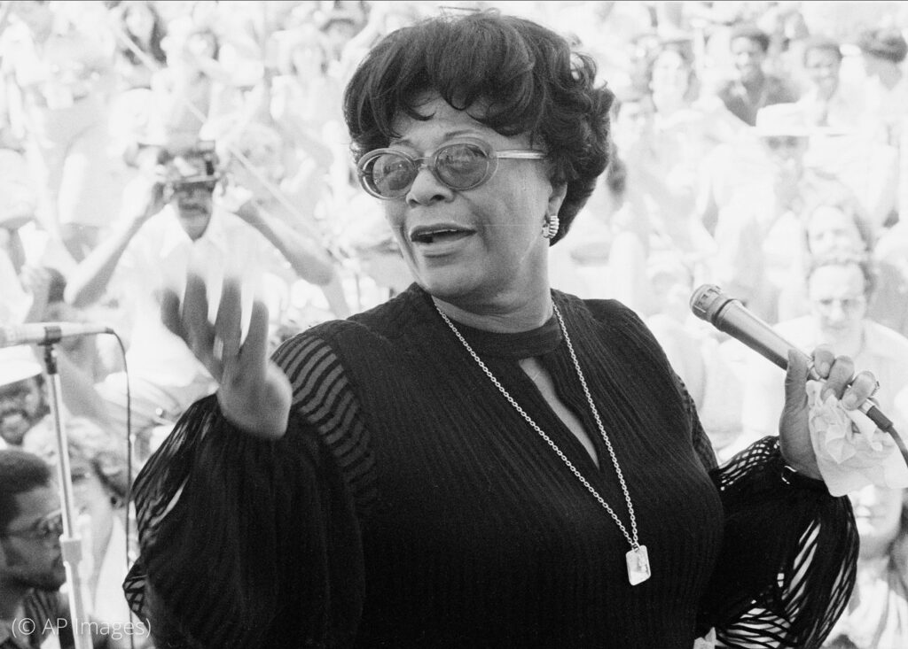 Ella Fitzgerald holding microphone and singing (© AP Images)