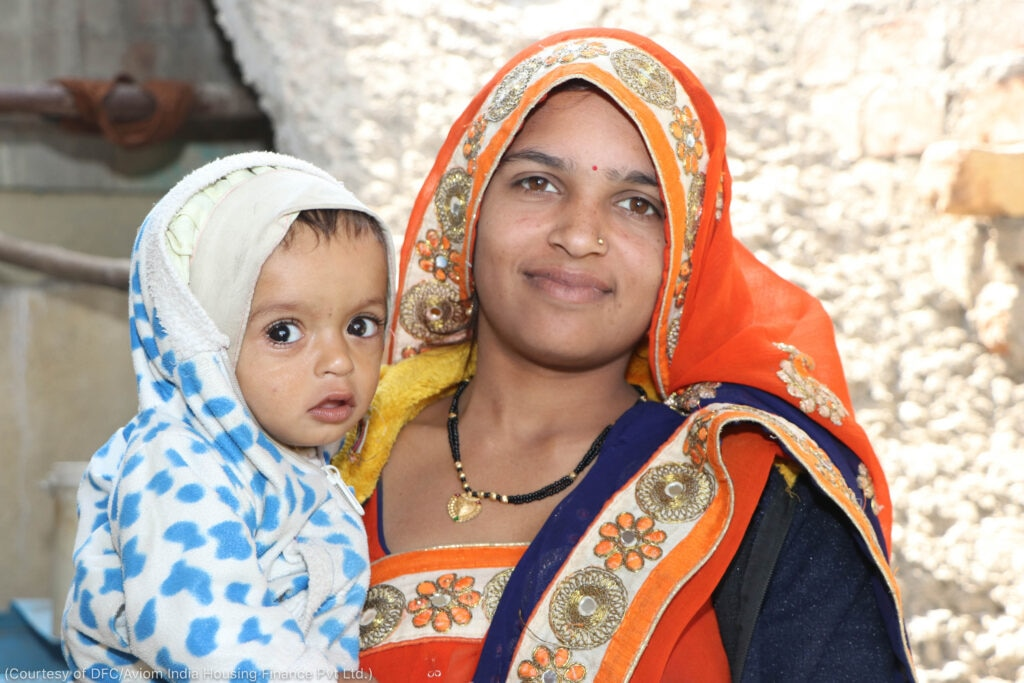 Young woman in sari and head covering holding baby (Courtesy of DFC/Aviom India Housing Finance Pvt Ltd.)