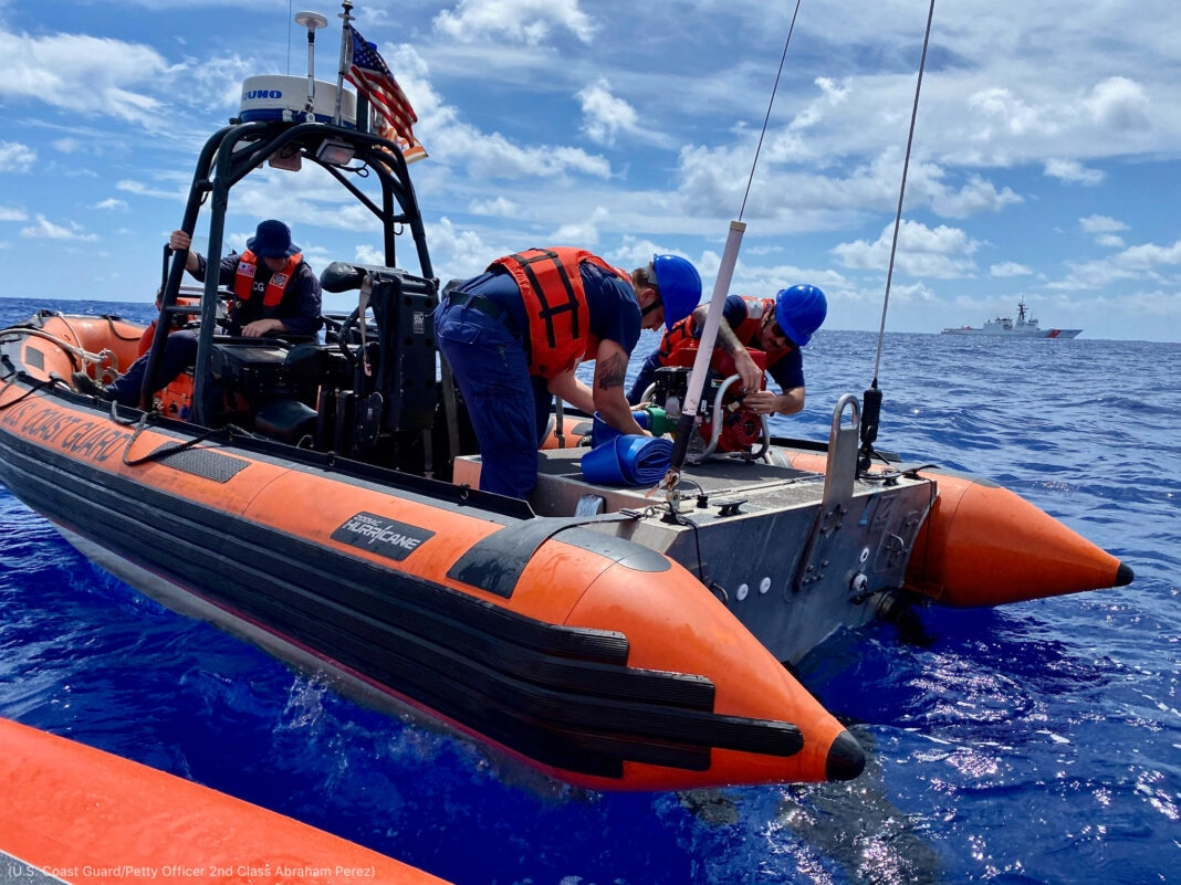 People setting up pump on vessel at sea (U.S. Coast Guard/Petty Officer 2nd Class Abraham Perez)