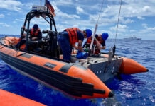 U.S. Coast Guard boat crew setting up dewatering pump at sea (U.S. Coast Guard/Petty Officer 2nd Class Abraham Perez)