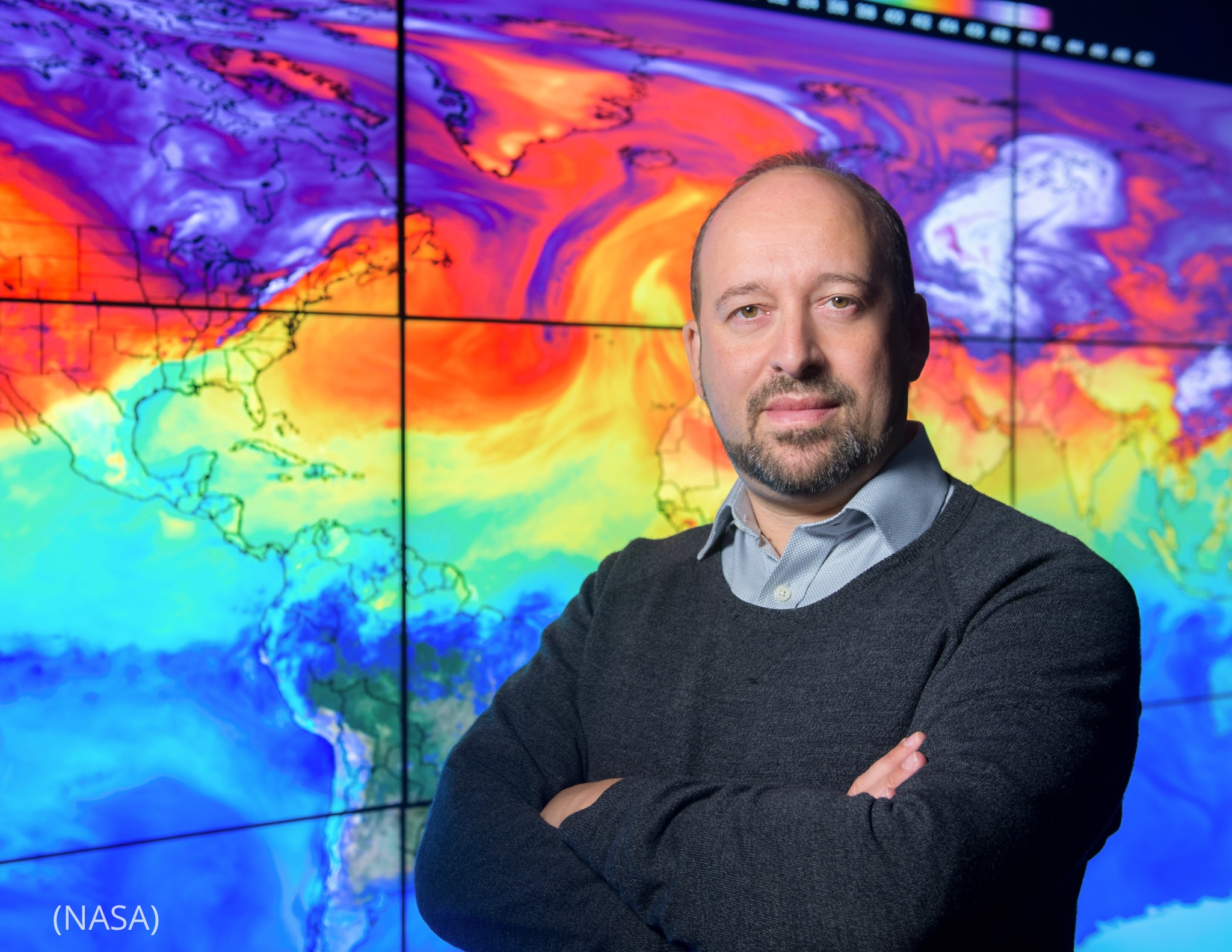 Gavin Schmidt de pie frente a un colorido mapa mundial en múltiples pantallas (NASA)