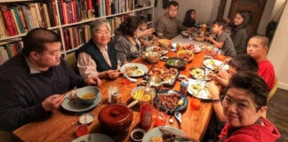 Generational Chinese family sitting around a table of food (© Hsaio-Ching Chou)