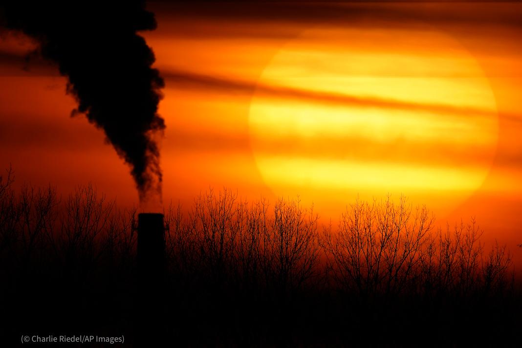 Silhouette d'une cheminée crachant une épaisse fumée noire devant un coucher de soleil (© Charlie Riedel/AP Images)