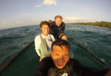 Three people smiling in boat (© Peace Corps)