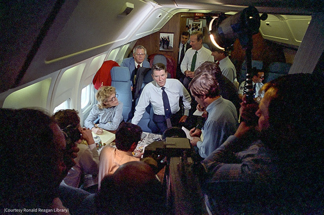 Man talking while surrounded by people on airplane (Courtesy Ronald Reagan Library)