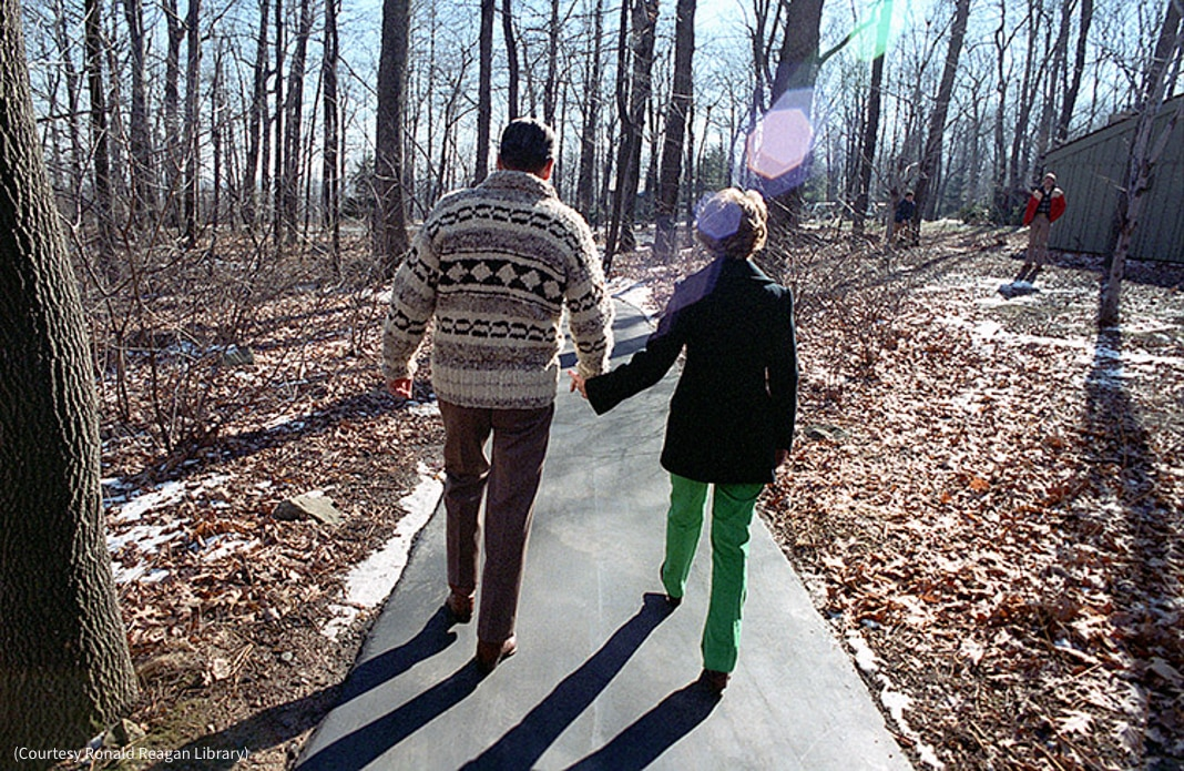 Man and woman holding hands while walking in woods (Courtesy Ronald Reagan Library)