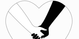 White and black arms with hands clasped inside heart-shaped outline (© Irina Dias/Shutterstock)