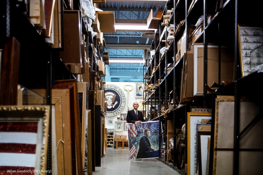 Man holding painting in storage room with packed shelves (Allan Goodrich/JFK Library)