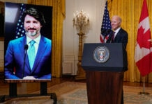 Justin Trudeau appears on a large screen next to President Biden who is standing behind a podium (© Evan Vucci/AP Images)