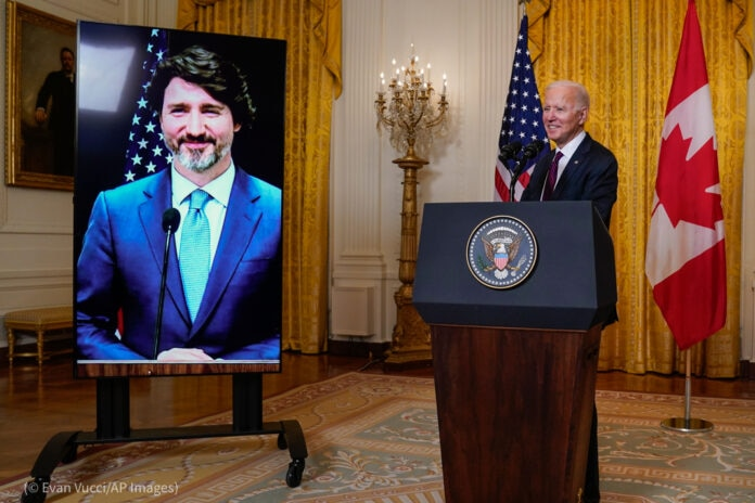 President Biden standing behind lectern next to screen showing Justin Trudeau (© Evan Vucci/AP Images)