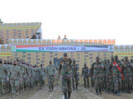Des militaires en ligne devant un mur sur lequel est accrochée une banderole portant l'inscription « Yudh Abhyas 20 » (U.S. Army/Staff Sgt. Joe Tolliver)