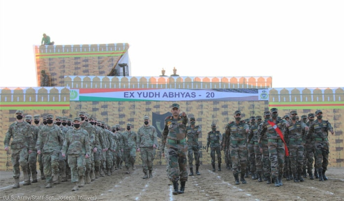 Formation of people in military uniforms standing by wall with Yudh Abhyas banner (U.S. Army/Staff Sgt. Joseph Tolliver)