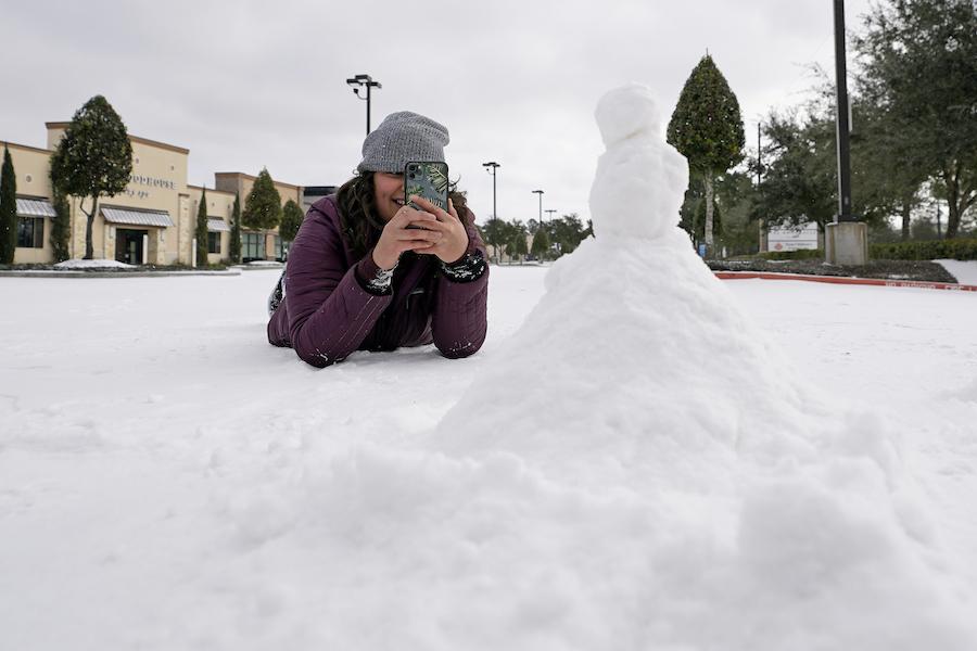 休斯顿一位女孩大雪过后玩堆雪人(照片:美联社)