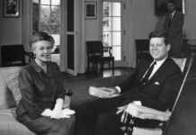 President John Kennedy meeting with a woman, both sitting (© Gibson Moss/Alamy)