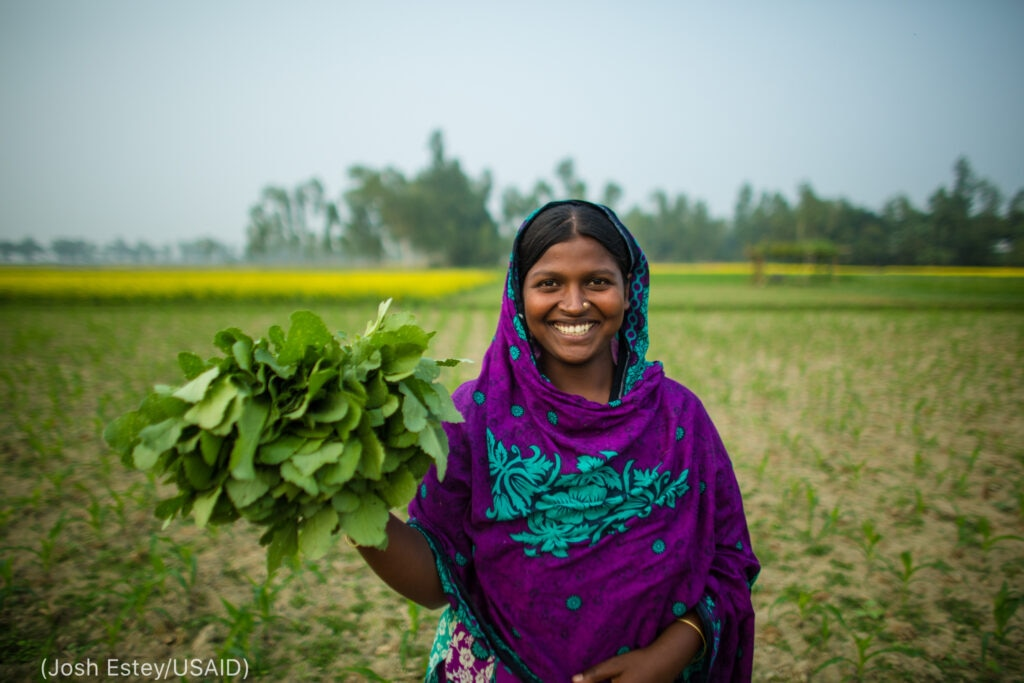 Smiling woman standing in field holding greens (Josh Estey/USAID)
