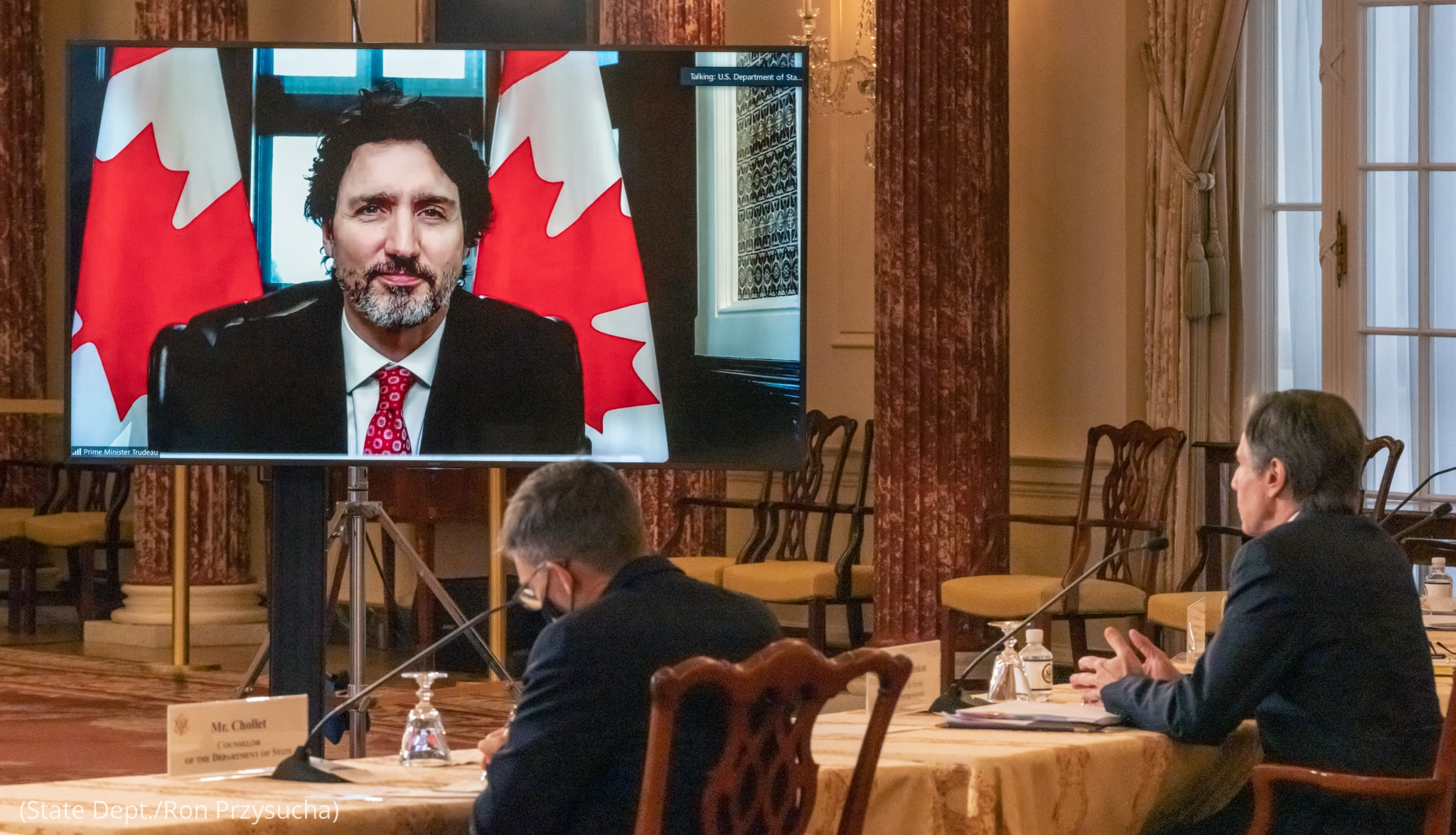Secretary of State Antony Blinken sitting at table while interacting with Justin Trudeau through screen as another man takes notes (State Dept./Ron Przysucha)