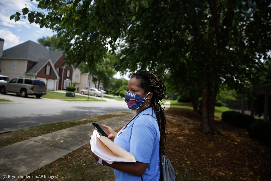 Woman with folder of papers and cellphone standing near neighborhood street (© Brynn Anderson/AP Images)