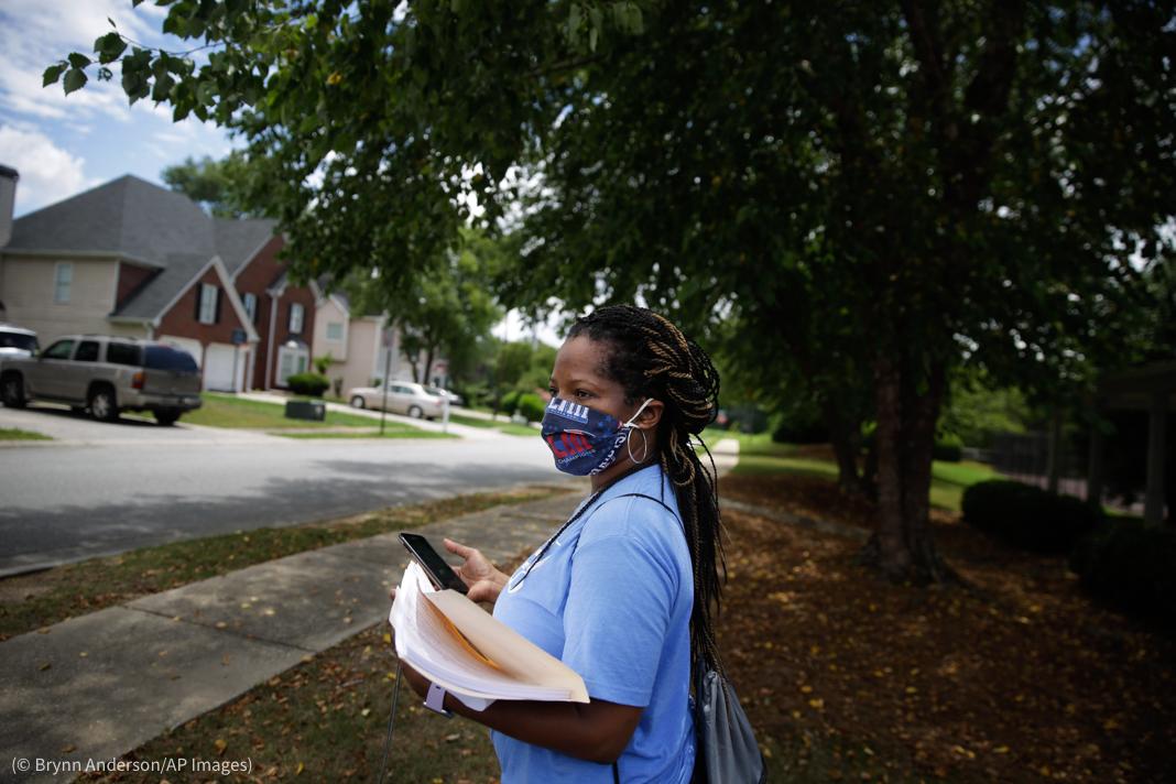 ایک عورت کاغذات اور موبائل فون ہاتھ میں پکڑے سڑک کنارے کھڑی ہے (© Brynn Anderson/AP Images)