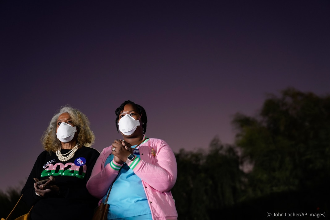 Two women looking into the distance at night (© John Locher/AP Images)