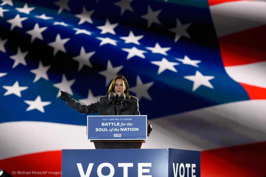 کملا ہیرس سٹیج پر تقریر کر رہی ہیں اور پس منظر میں امریکی پرچم دکھائی دے رہا ہے (© Michael Perez/AP Images)
