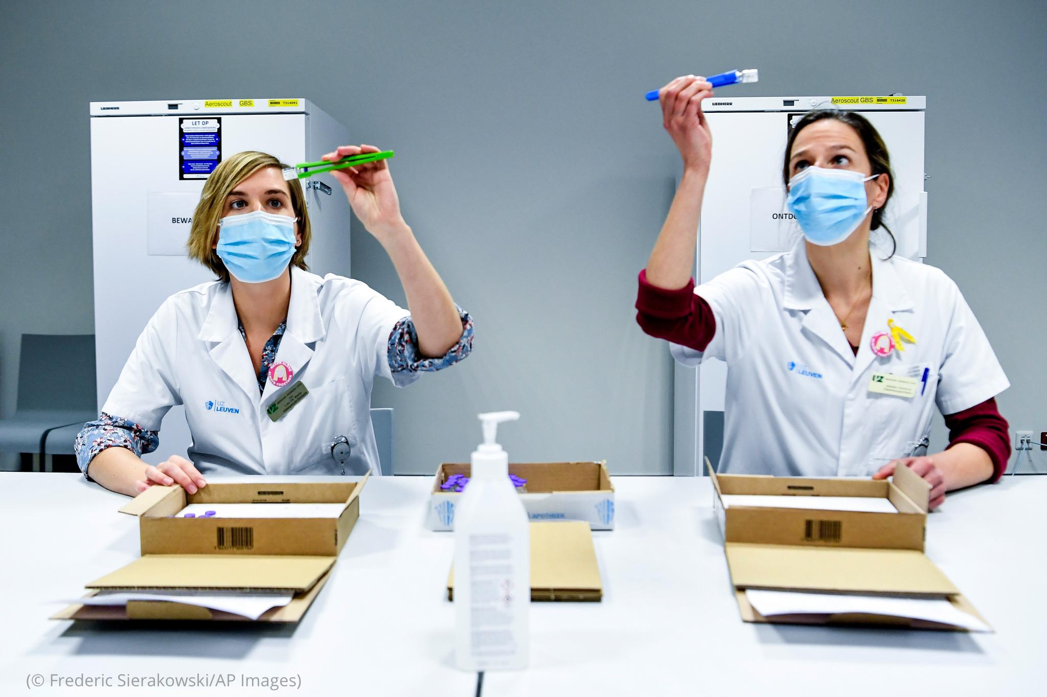 Deux personnes en blouse de laboratoire en train d'inspecter des fioles (© Frederic Sierakowski/AP Images)