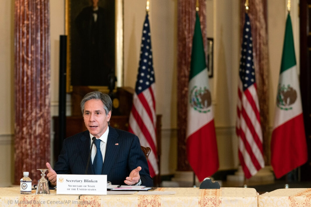 Secretary of State Antony Blinken speaking at table with U.S. and Mexican flags in background (© Manuel Balce Ceneta/AP Images)