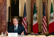 Secretary of State Antony Blinken speaking while sitting at table with U.S. and Mexican flags in background (© Manuel Balce Ceneta/AP Images)