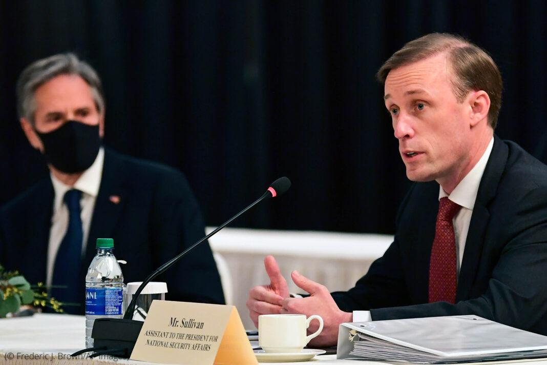 Antony Blinken in mask listening to Jake Sullivan speak (© Frederic J. Brown/AP Images)