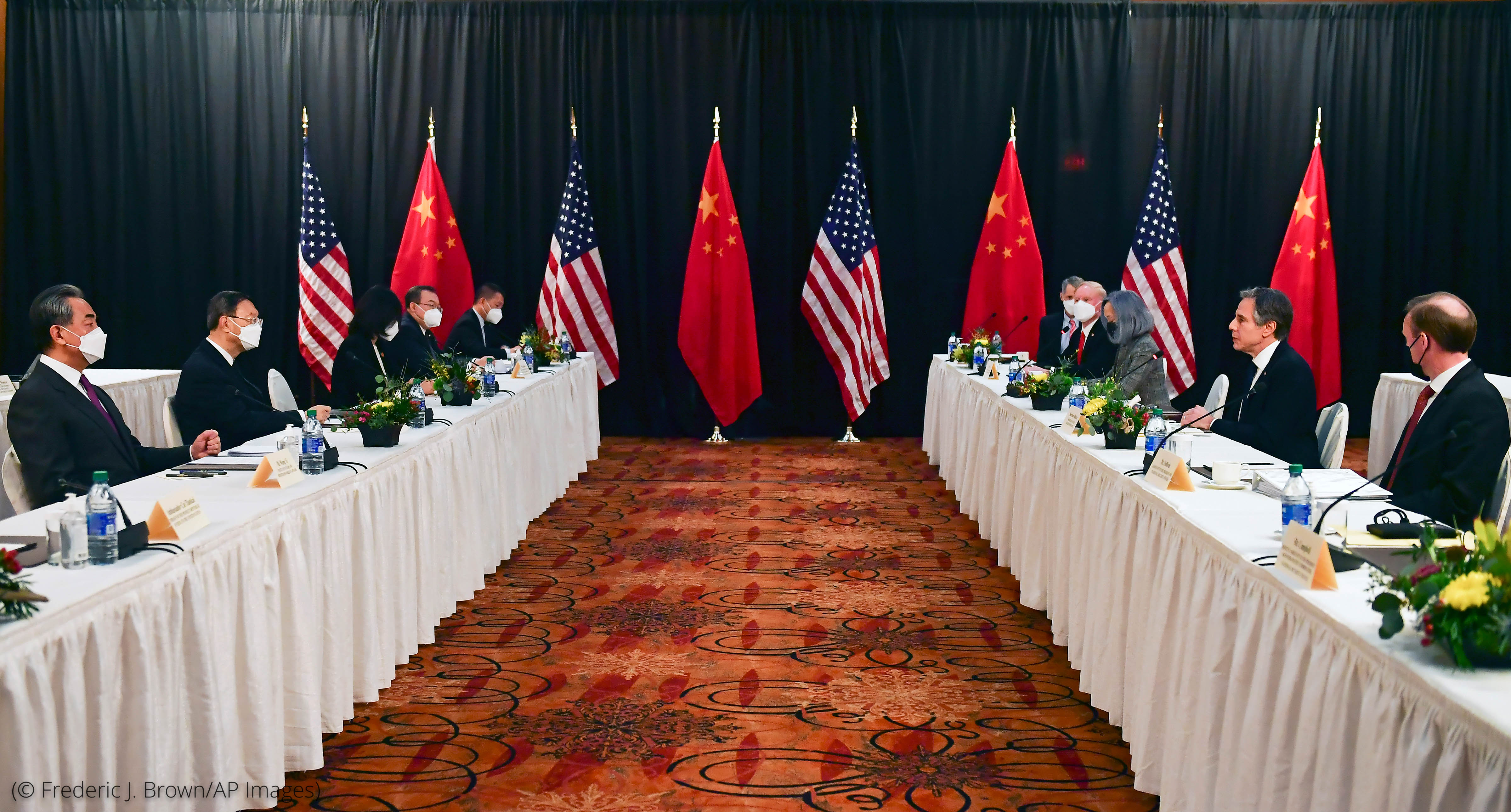 Men sitting at two long, facing tables with white tablecloths, with line of U.S. and Chinese flags at one end (© Frederic J. Brown/AP Images)