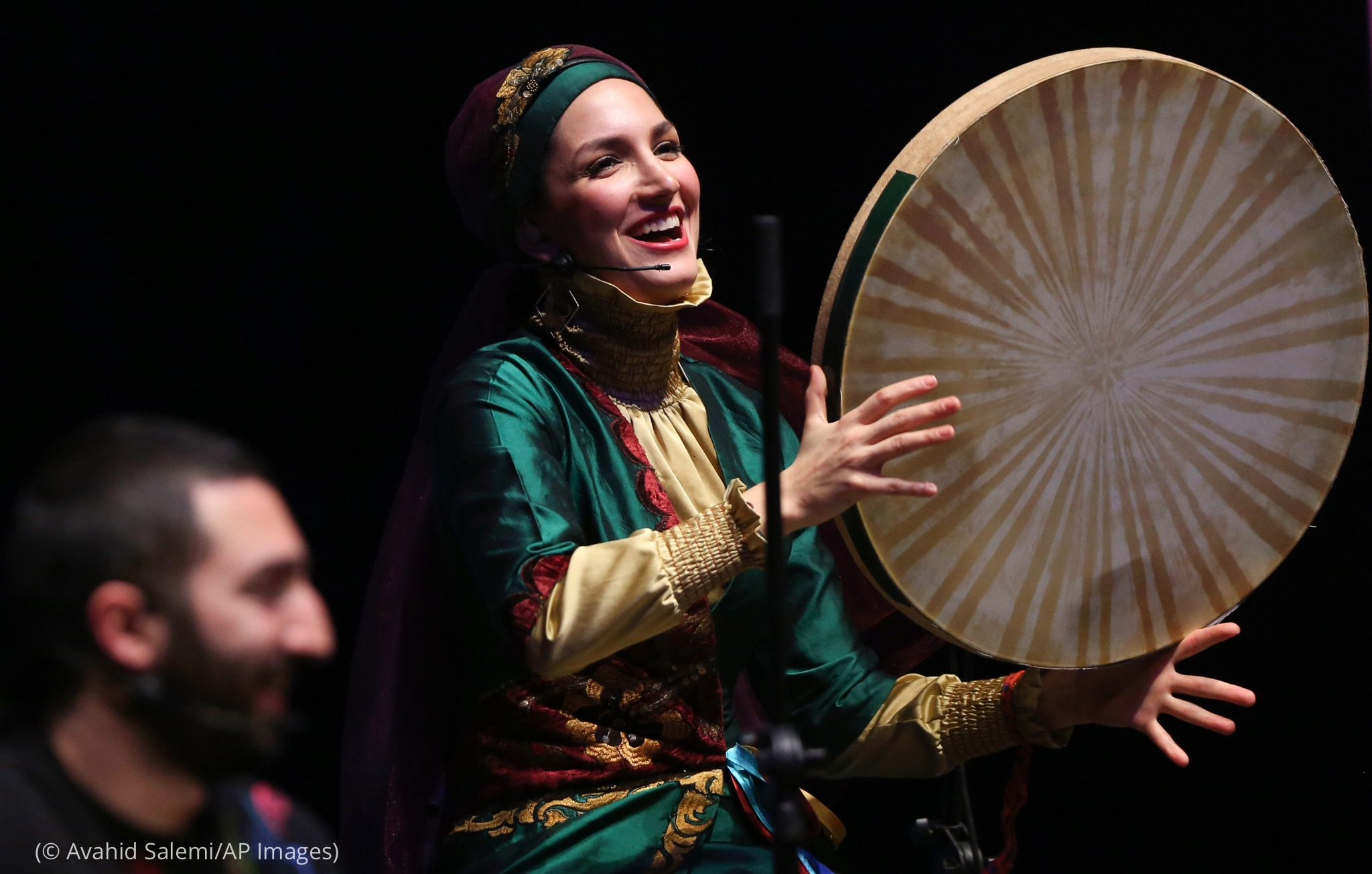 رنگ برنگا لباس پہنے اور سر پر دوپٹہ لپیٹے ایک عورت دف بجا رہی ہے اور اُس کے ساتھ ایک آدمی بیٹھا ہوا ہے (© Avahid Salemi/AP Images)