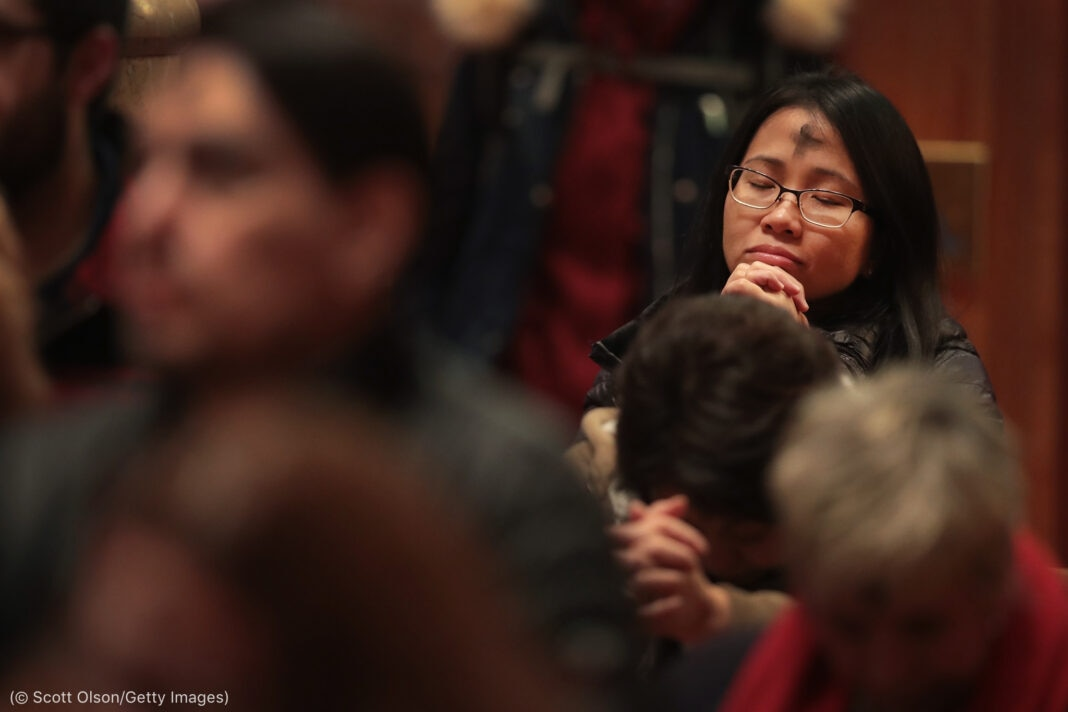 Praying Asian woman with forehead marked with cross (© Scott Olson/Getty Images)