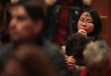 Asian woman with a cross made with ashes praying at church (© Scott Olson/Getty Images)