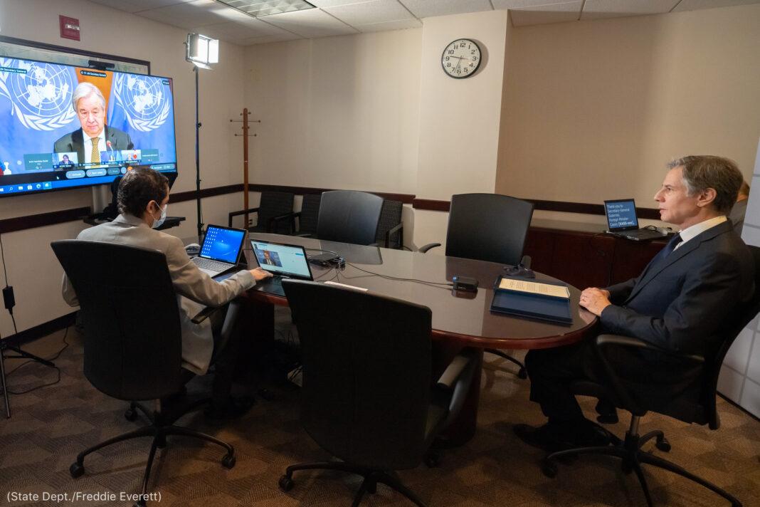 Antony Blinken (dcha.) y una persona con computadoras portátiles sentados a una mesa de conferencias, con una pantalla de una televisión en la pared (Depto. de Estado/Freddie Everett)