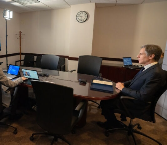 Antony Blinken (right) and person with laptops sitting at conference table, with TV screen on wall (State Dept./Freddie Everett)