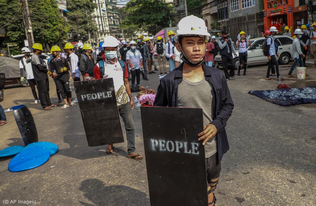 """Grupo de manifestantes com capacetes de construção em uma rua, dois deles segurando placas com a palavra """"Pessoas"""" impressa nelas (© AP Images)"""