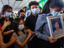 ایک جنازے میں شامل لوگوں نے ایک دوسرے کو پکڑا ہوا ہے اور رو رہے ہیں (© AP Images)