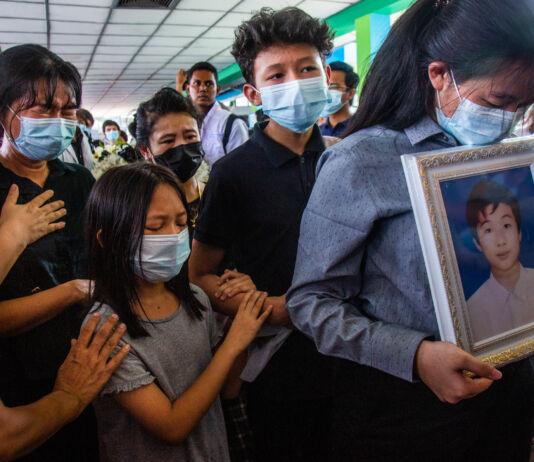 Orang-orang saling berpelukan dan menangis di pemakaman (© AP Images)