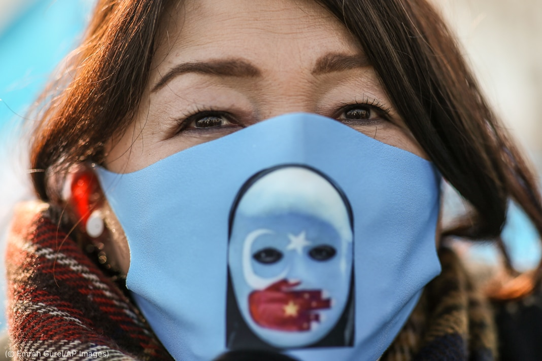 Woman wearing mask with picture of Chinese flag shaped like a hand covering mouth of white-masked face (© Emrah Gurel/AP Images)