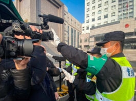 Police officers blocking camera lenses with hands outside building (© Leo Ramirez/AFP/Getty Images)
