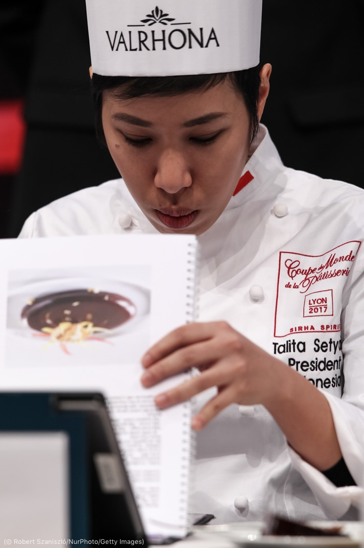 Woman in chef's uniform holding spiral-bound book and looking down (© Robert Szaniszló/NurPhoto/Getty Images)