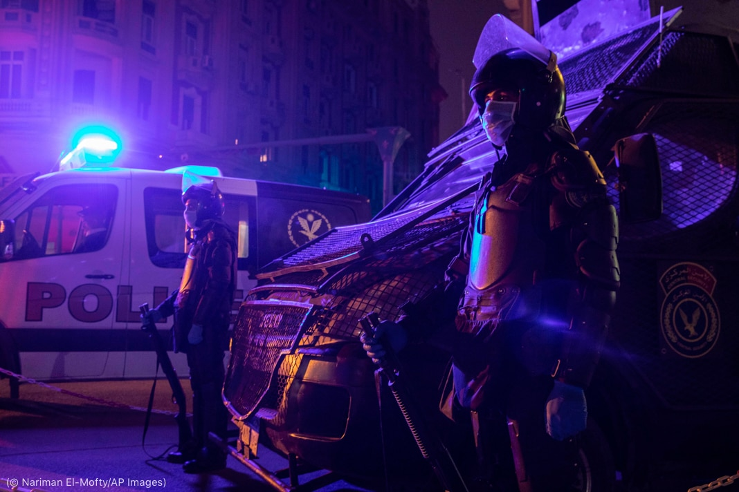 Two officers with rifles standing guard near police vehicles at night (© Nariman El-Mofty/AP Images)