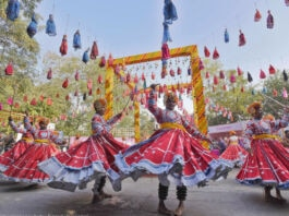 People in brightly colored costumes dancing (© Sanjeev Verma/Hindustan Times/Getty Images)