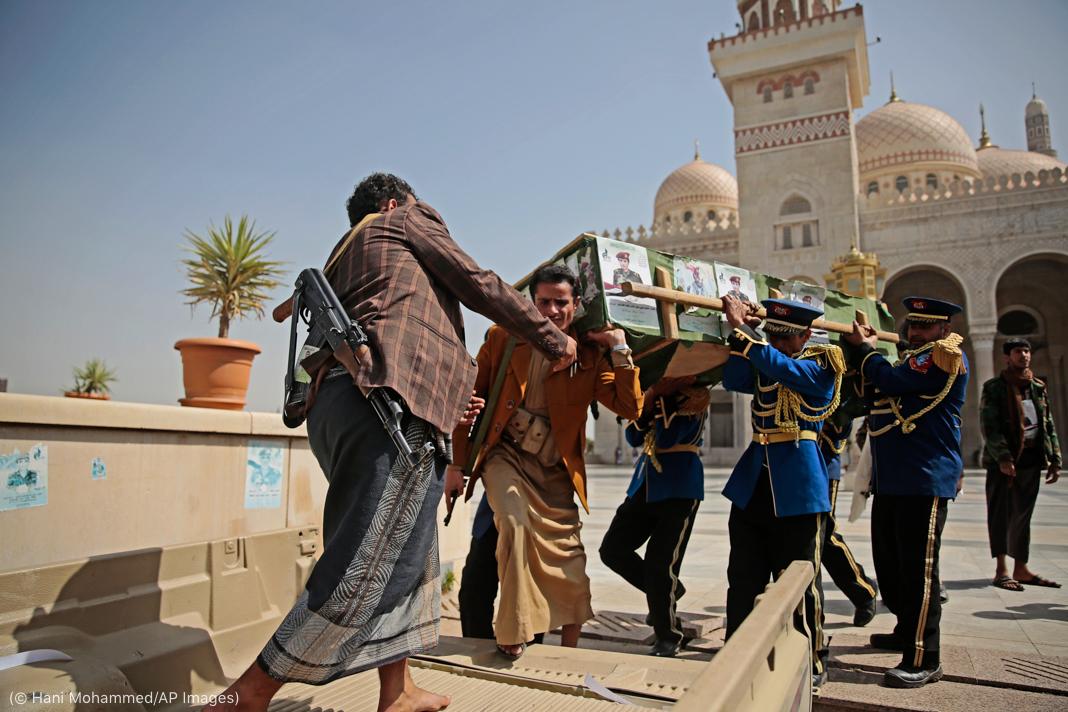 Hombres armados vestidos de civiles y hombres con uniforme azul llevan un ataúd (© Hani Mohammed/AP Images)