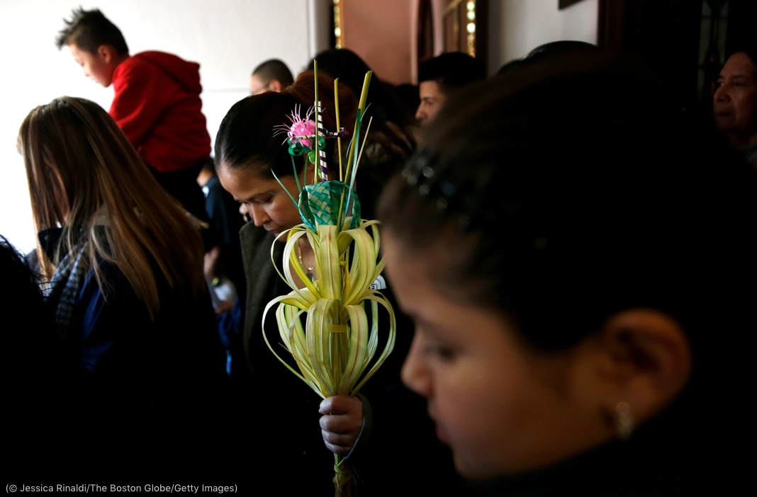Woman carrying staff with flowers and palm leaves among group of people (© Jessica Rinaldi/The Boston Globe/Getty Images)