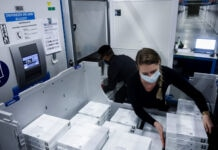 A man and a woman put vaccine boxes in freezer (© Kenzo Tribouillard/AFP/Getty Images)