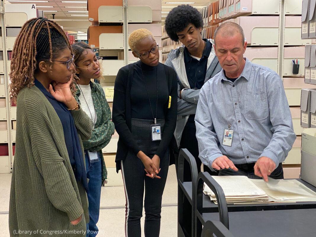 Des jeunes gens rassemblés autour d'un homme qui pointe du doigt des documents sur un chariot (Bibliothèque du Congrès/Kimberly Powell)
