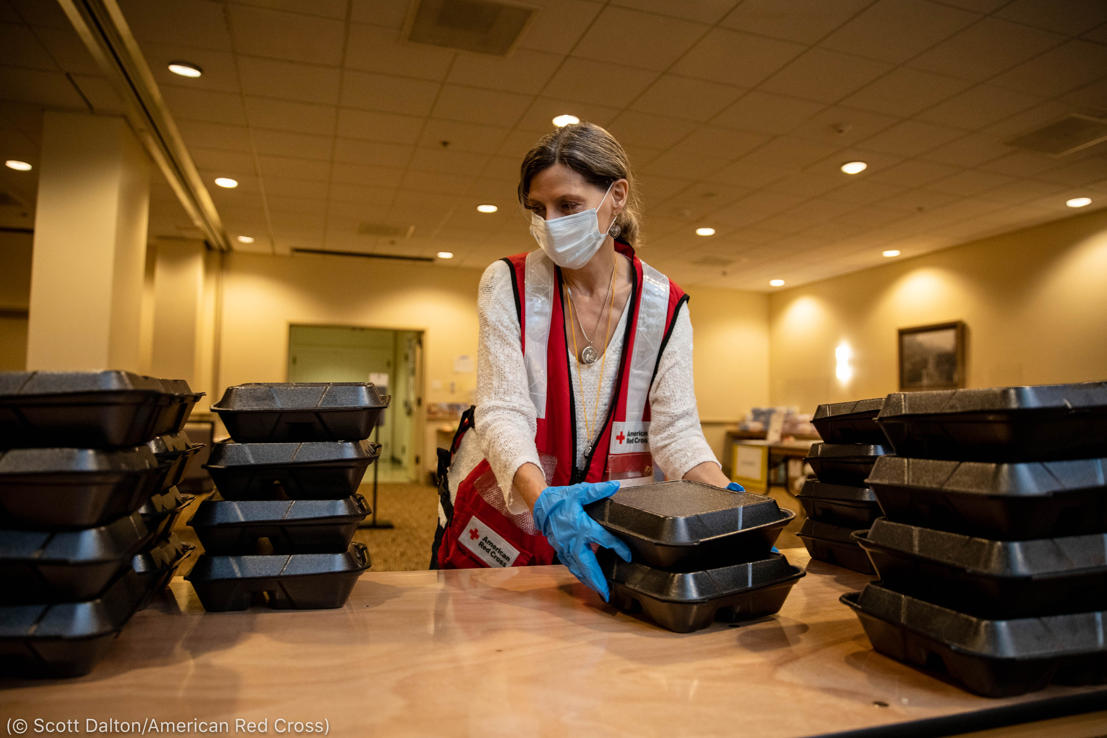 Woman wearing protective mask and gloves while stacking boxes on counter (© Scott Dalton/American Red Cross)