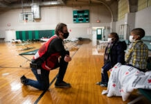 Man kneeling and talking to children sitting on cot in gymnasium (© Scott Dalton/American Red Cross)