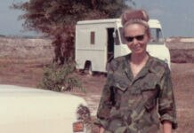 Woman in camouflage uniform smiling and standing in front of vehicle (Collection of the National Museum of American Diplomacy)