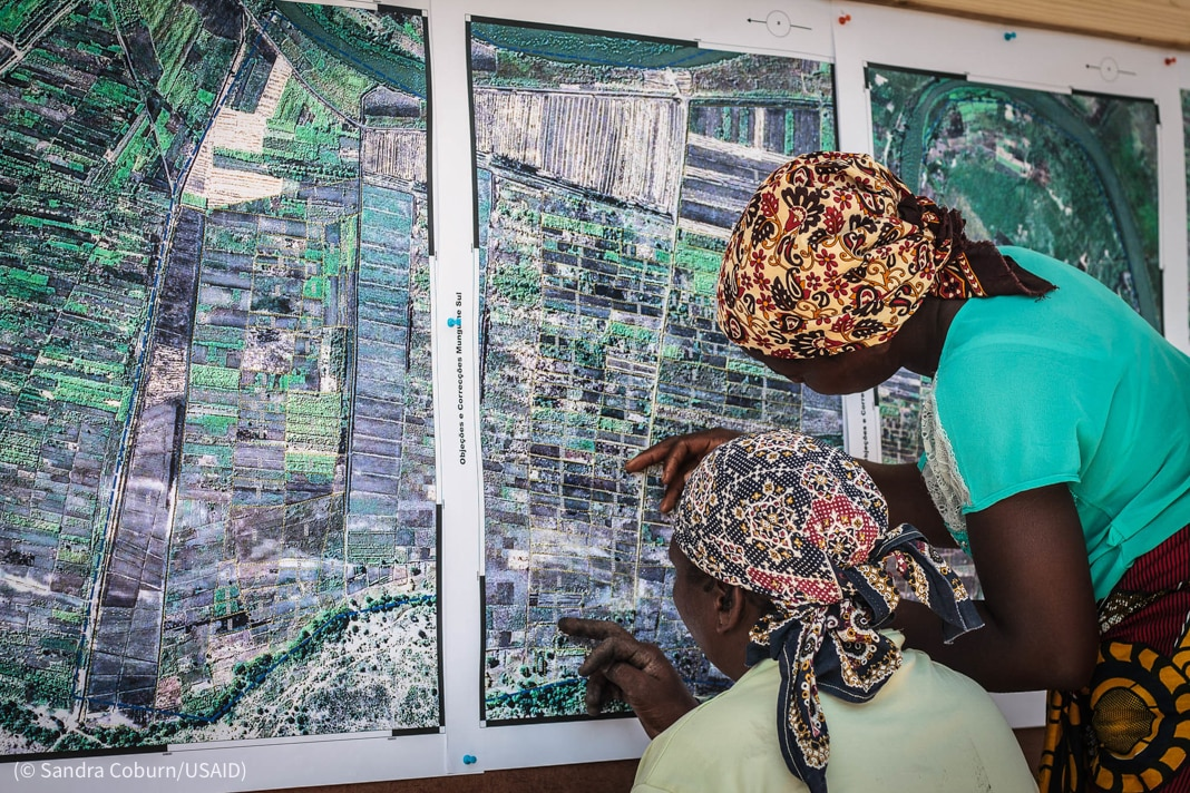 Two women examining a map (© Sandra Coburn/USAID)